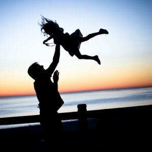 niña brincando con su padre