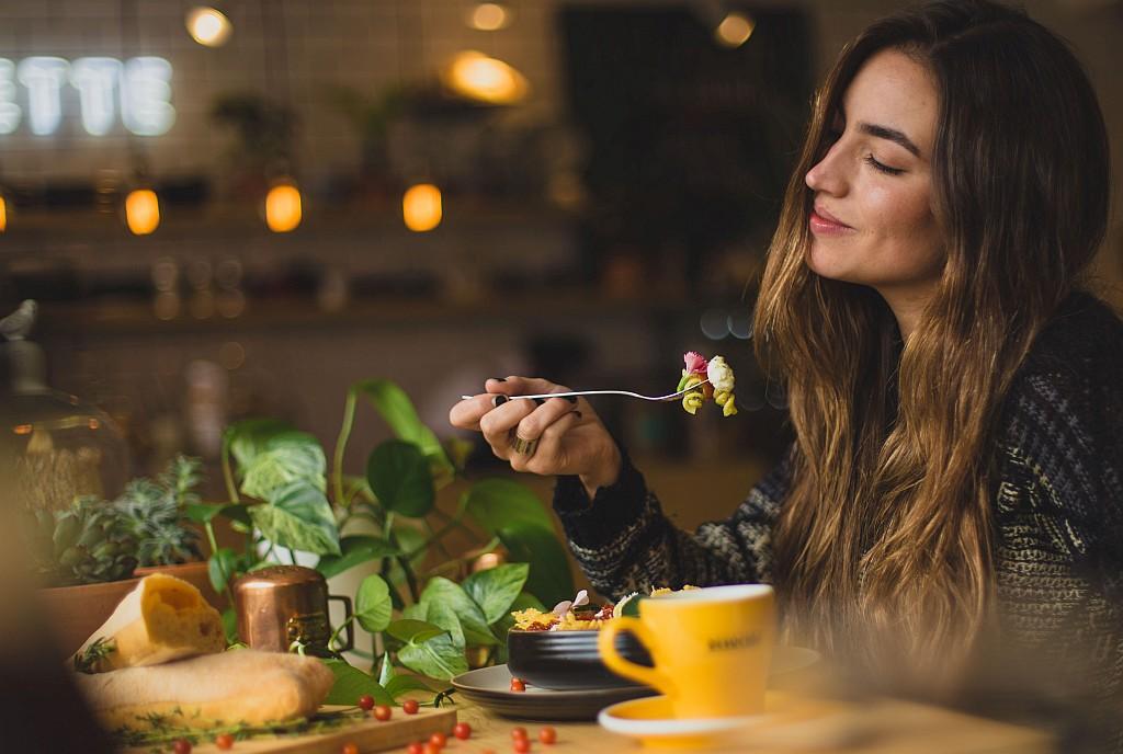 mujer comiendo en restaurante